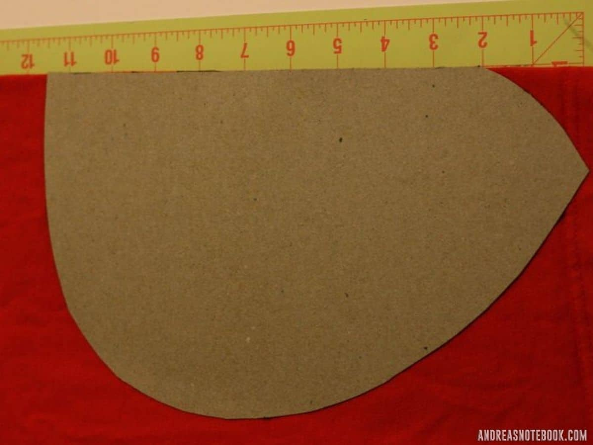 yellow cutting mat on floor. Cardboard shaped like one ladybug wing on top of red fabric.