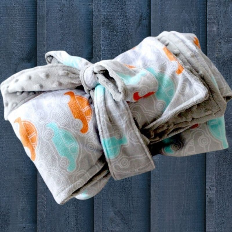 rolled up fuzzy baby blanket sewing pattern. Gray fabric with orange and aqua dino on a navy blue background