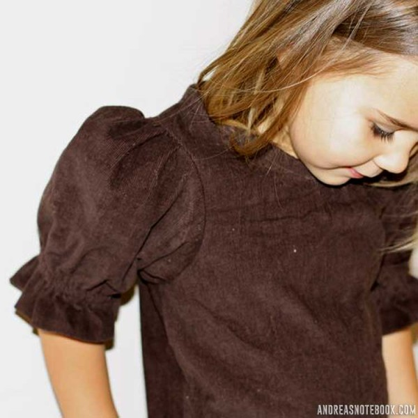 little girl with brown hair and golden skin wearing brown corduroy top with puffed sleeves
