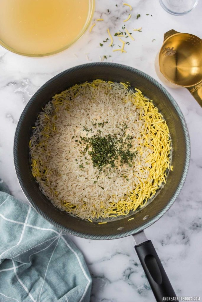 sauteed pasta with rice and spices on top in a black saucepan