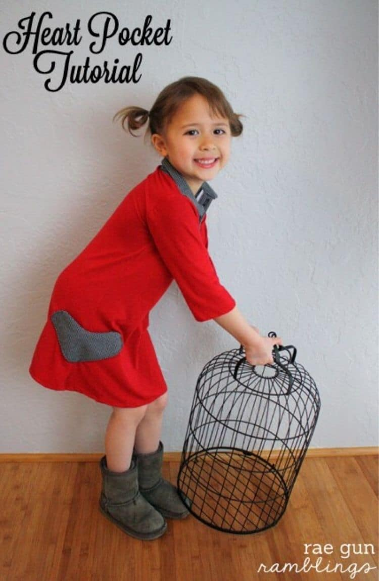 little girl in red long sleeve dress with gray heart pocket holds black wire bird cage. White all and wood floor in background