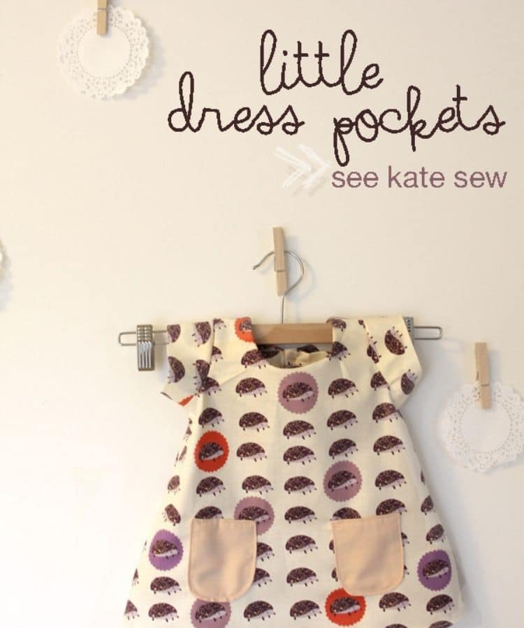 """white wall with tiny dress hanging on a hanger attached to wall. Dress is white with purple patter and light pink front pockets. Text on image says """"little dress pockets see kate sew"""""""