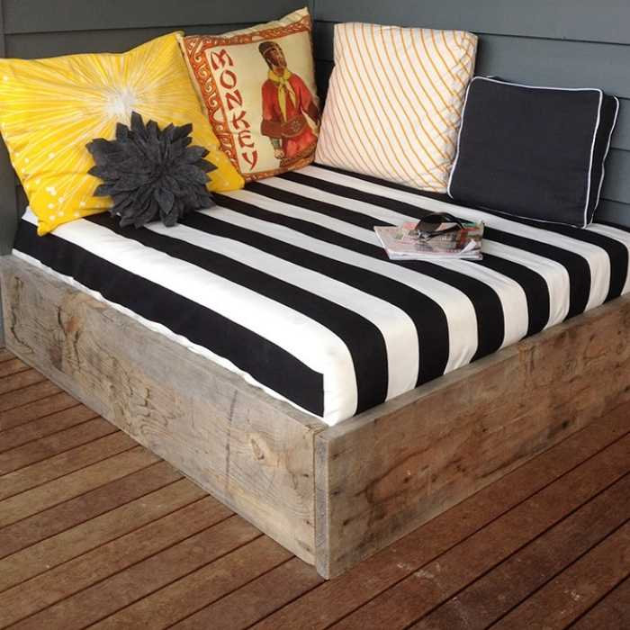 wood frame daybed on deck with black and white bedding with yellow pillows