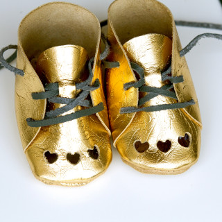 Gold baby booties with heart cutouts