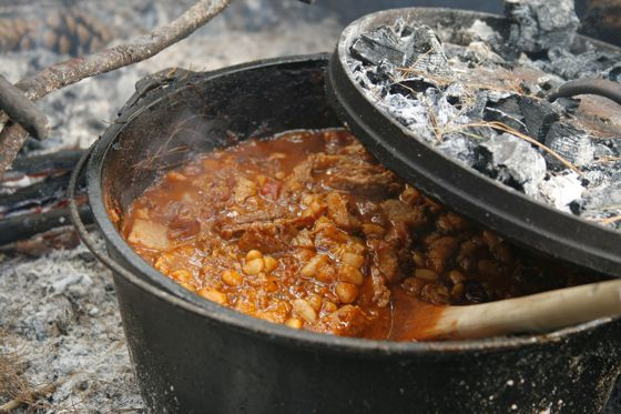 Slow cook chili over a campfire using a dutch oven