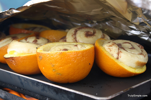 Bake a cinnamon roll in an orange over a campfire