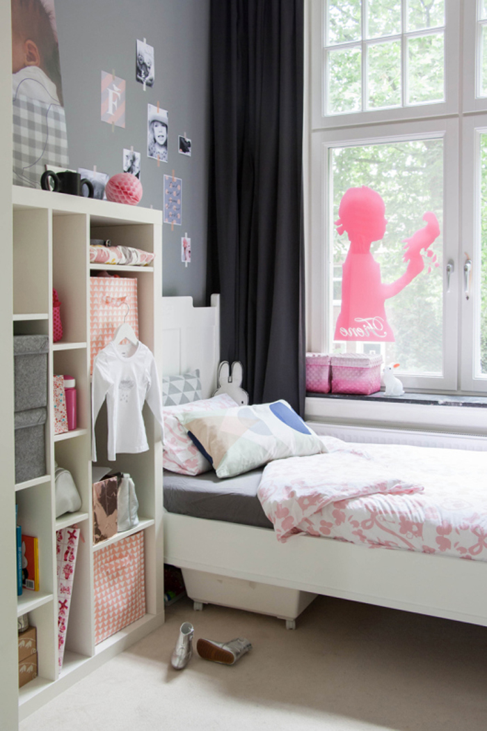 small girls bedroom with storage and pink decal