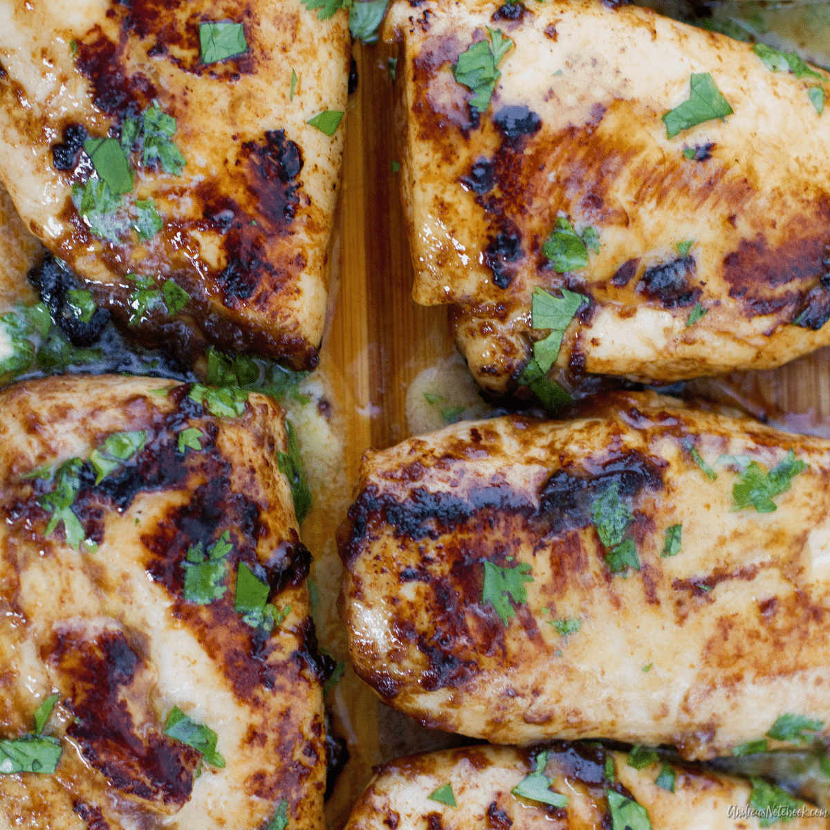 juicy cooked barbecue cilantro lime chicken breasts on a cutting board with cilantro on top