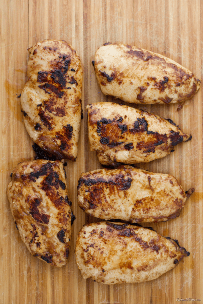 juicy cooked chicken breasts on a cutting board with cilantro on top