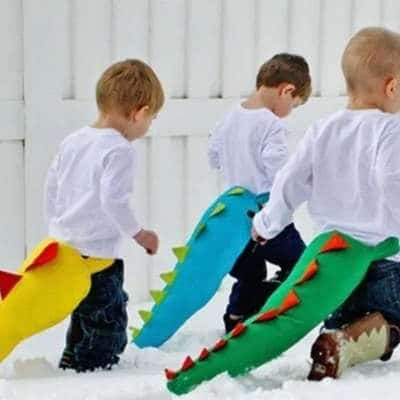 3 children with short hair walking in snow with white long sleeve shirts and dinosaur tails