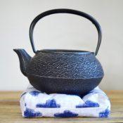 black cast iron teapot on white and blue tea trivet