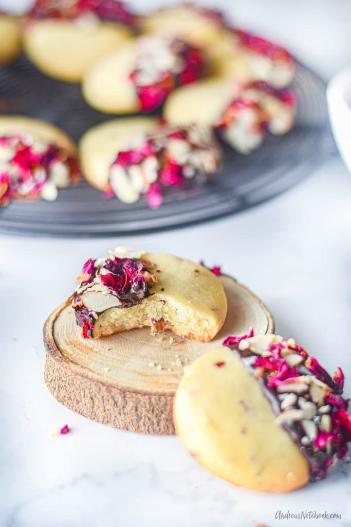 bite out of shortbread cookie that's been half dipped in chocolate and rolled in almonds and rose petals