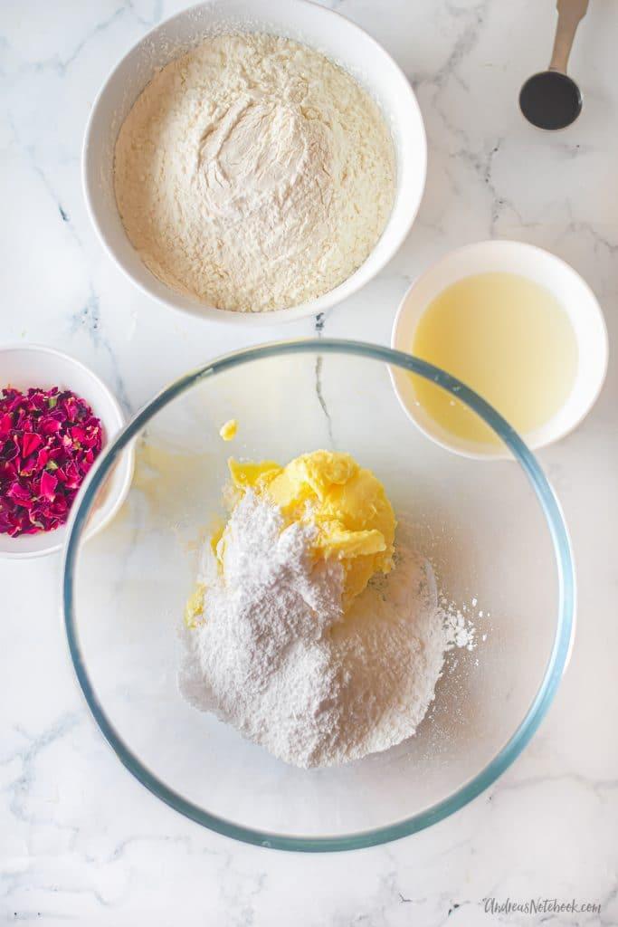 rose vanilla shortbread cookies ingredients in bowls - flower, butter, milk, sugar, rose petals
