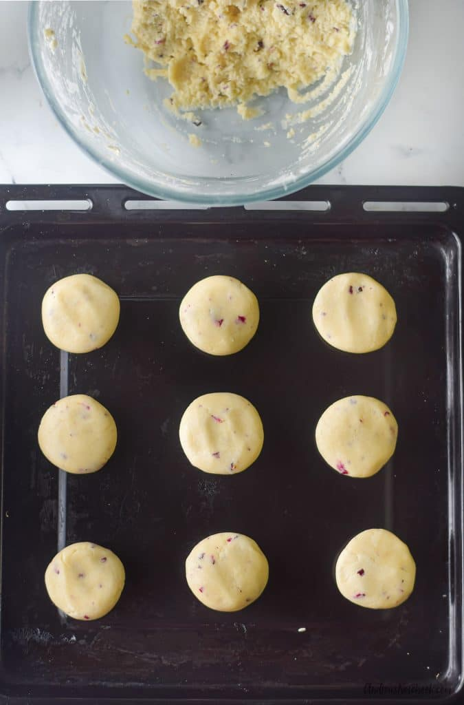 9 small round cookie dough balls on black baking sheet