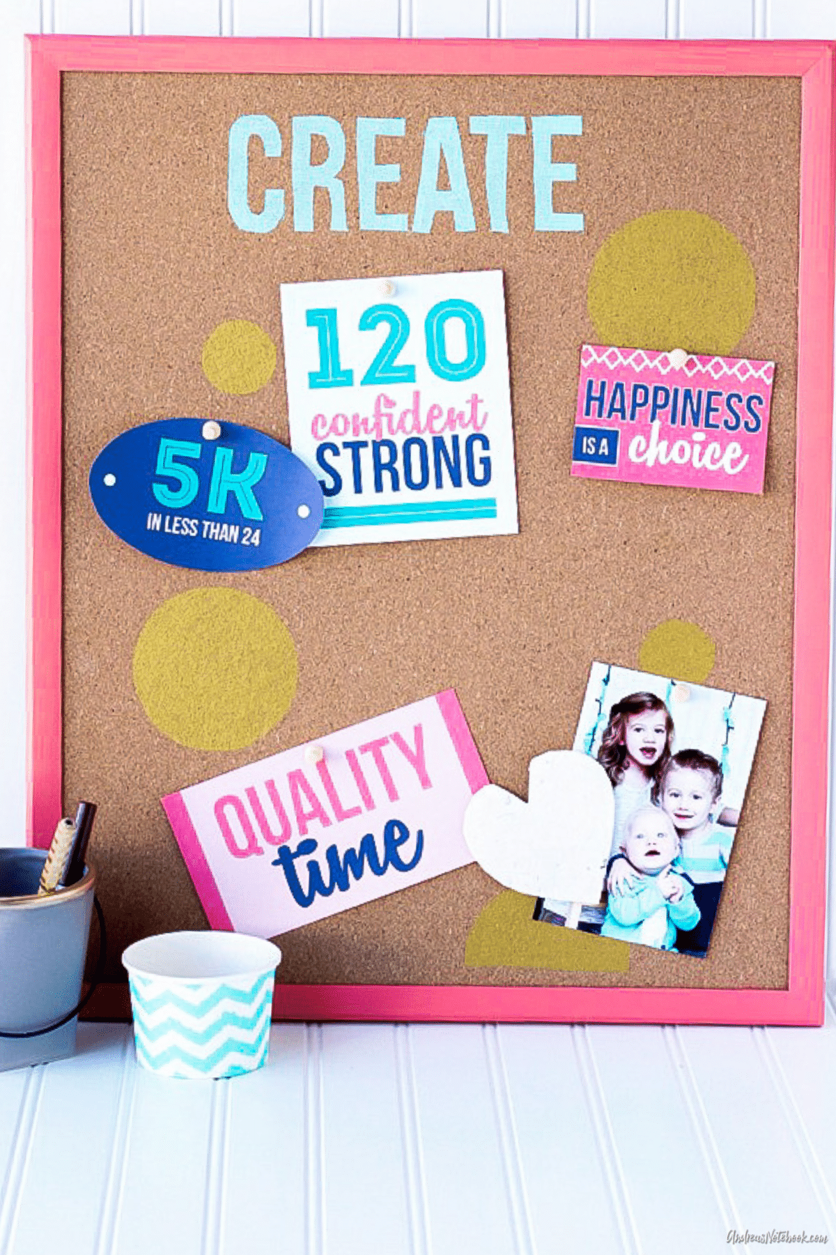 vision board cork board with pink frame and pinned stickers and photos