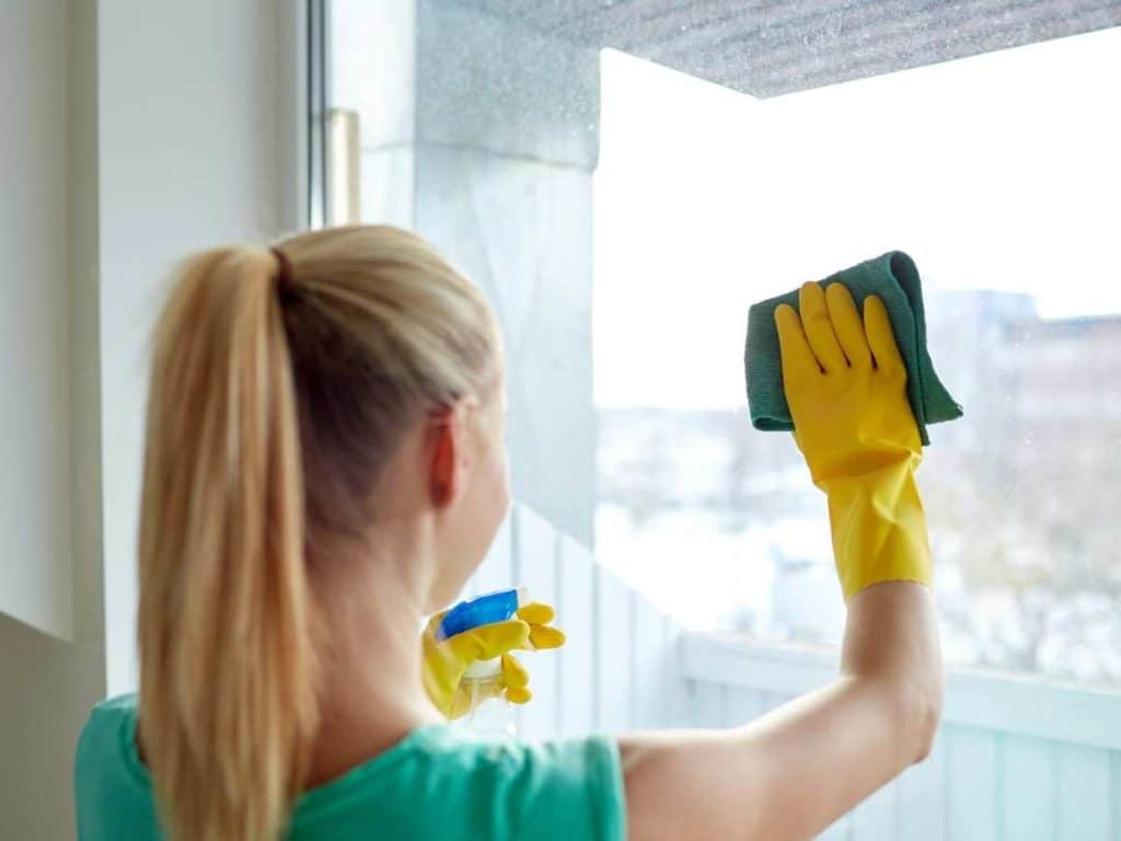 woman with blonde pony tail uses yellow rubber gloves and green cloth to wipe large window