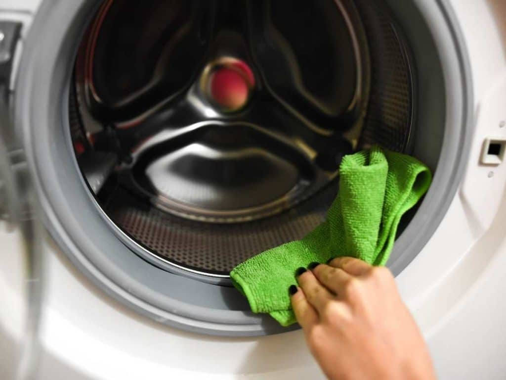 Hand using green microfiber cloth and vinegar cleaning solution wiping down the rubber on a washing machine.