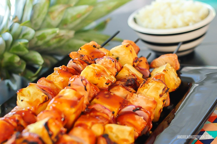black rectangular plate with a stack of kabab skewers with pineapple, pineapple and onion with a glaze on top