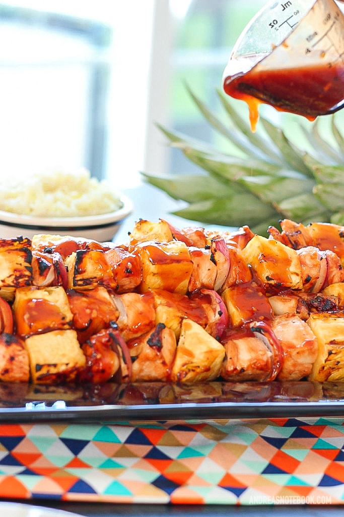 black rectangular plate with a stack of kabab skewers with pineapple, pineapple and onion with a glaze on top being dripped onto kabobs from a measuring cup from above
