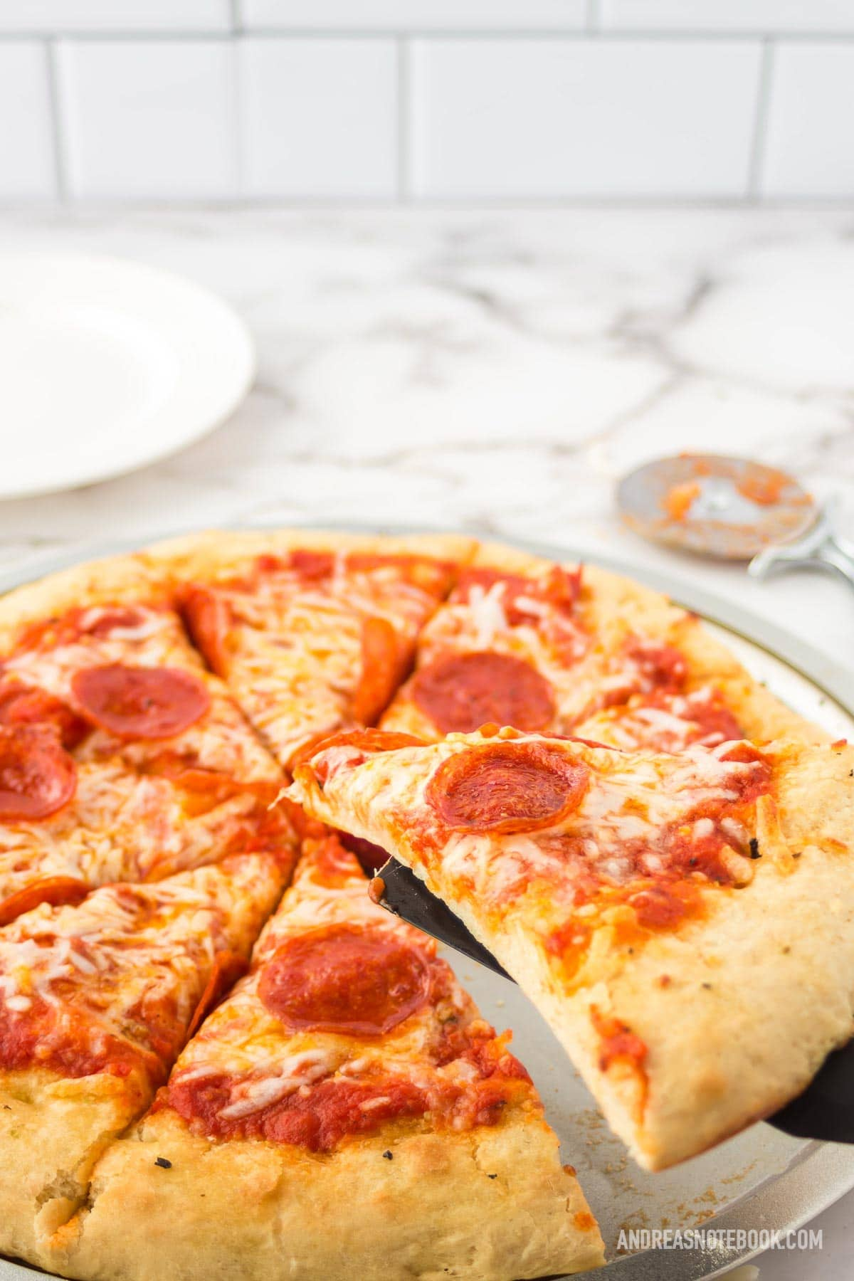 whole pepperoni pizza on white marble counter with subway tile background