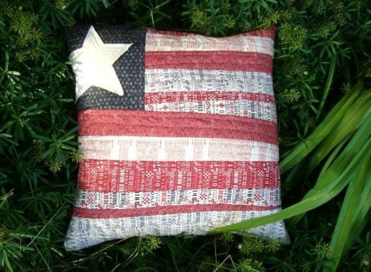 quilted flag pillow with white and red stripes and one star.
