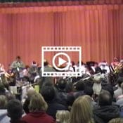 red stage curtain with band kids up front and backs of heads of people in the audience