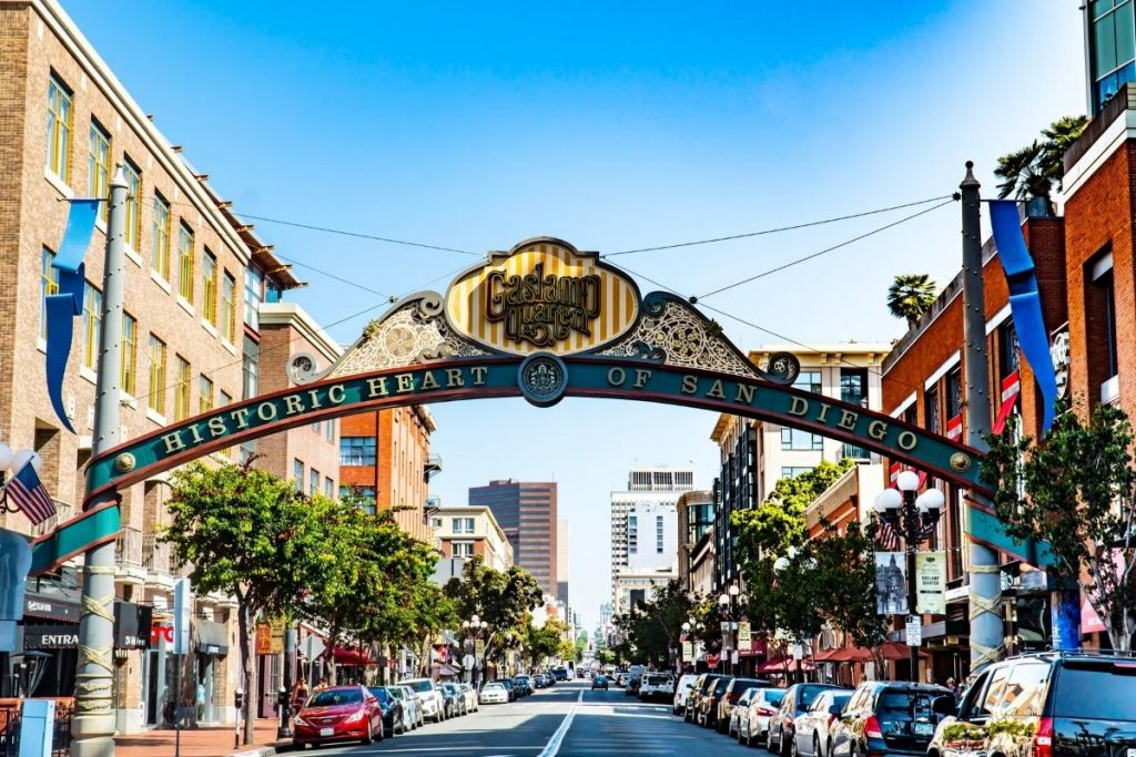 The Gaslamp Quarter sign arching over the street is the beginning of the gaslamp quarter. The tourist attraction is one of the best things to do in San Diego. Four to five story buildings on each side of the street with cars parked all along the street.