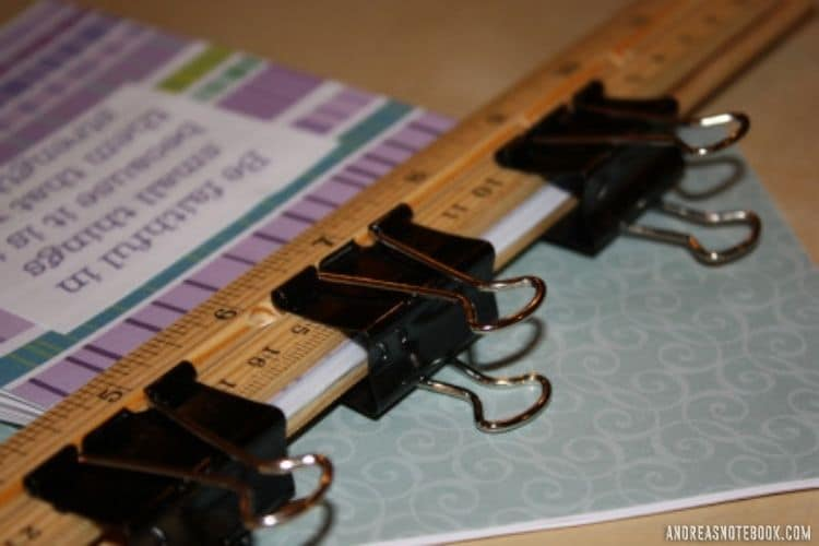Two wood rulers and three black binder clips clamping down a stack of papers with decorative paper on top in photo of how to make a notepad. Clamps used to hold DIY notepad together while the glue for binding notepads (padding compound) dries.