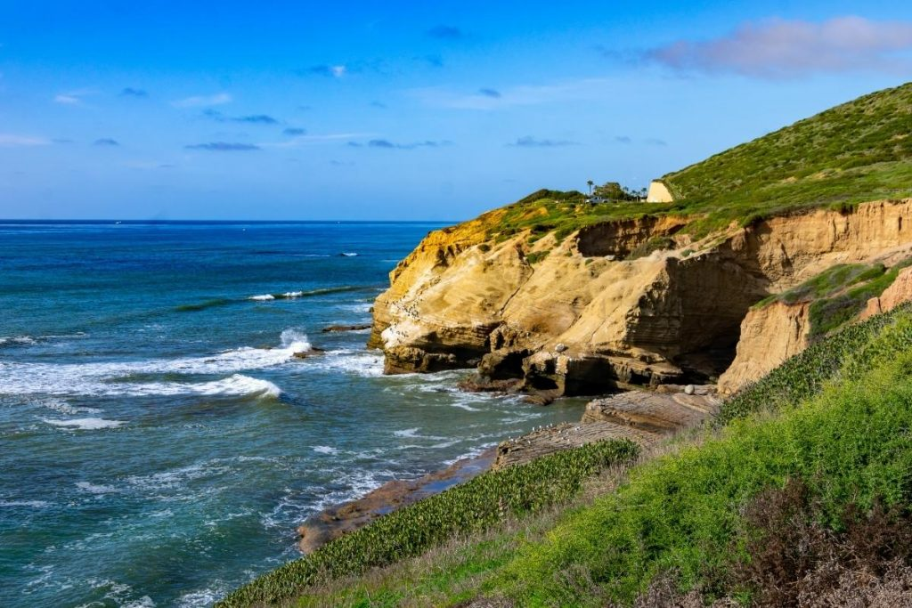 blue sky, green hills, brown cliffs and green ocean with waves