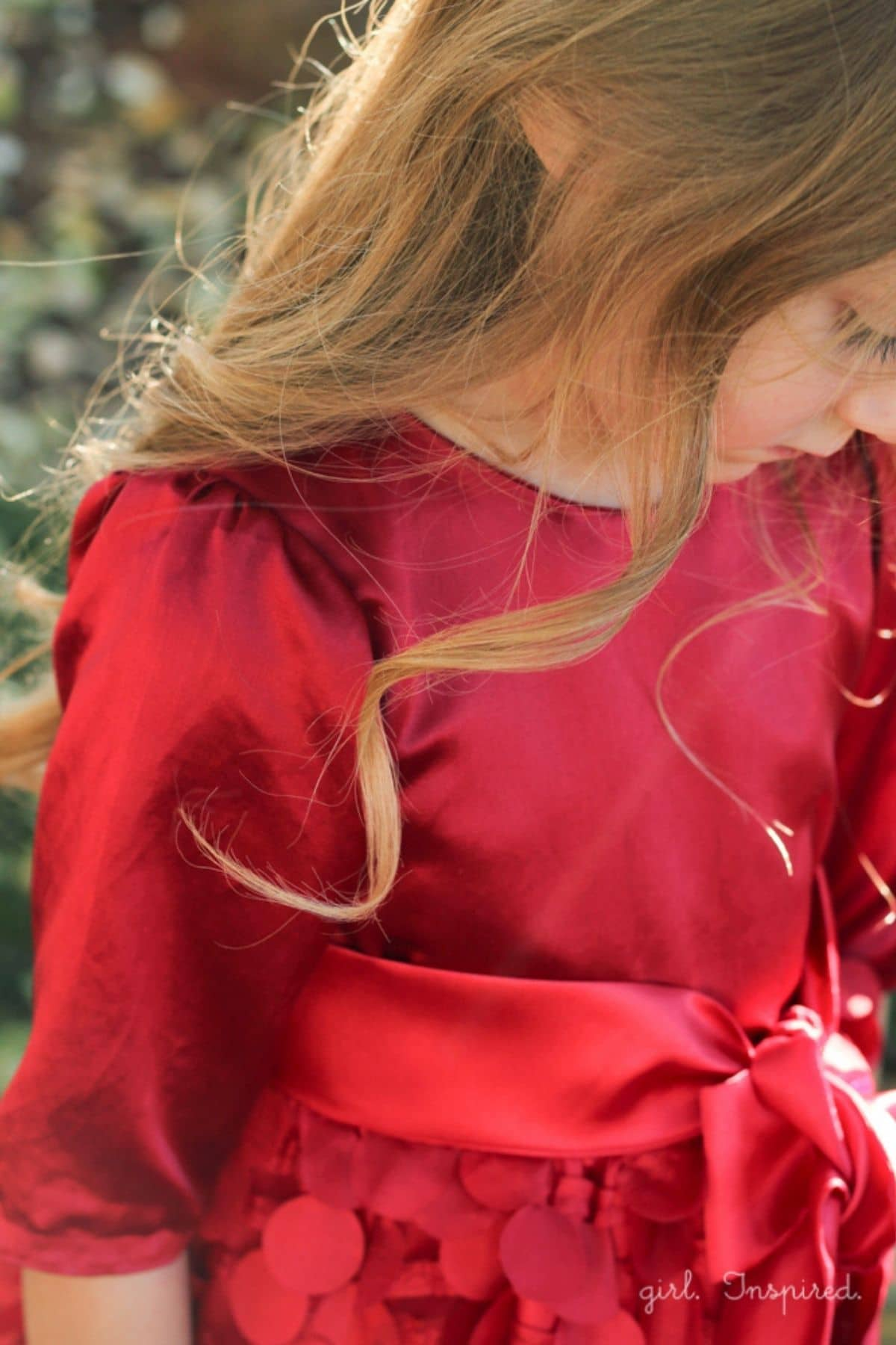 girl in red satin dress with puffed long sleeve. Image from her waist to mid face. Long brown hair.
