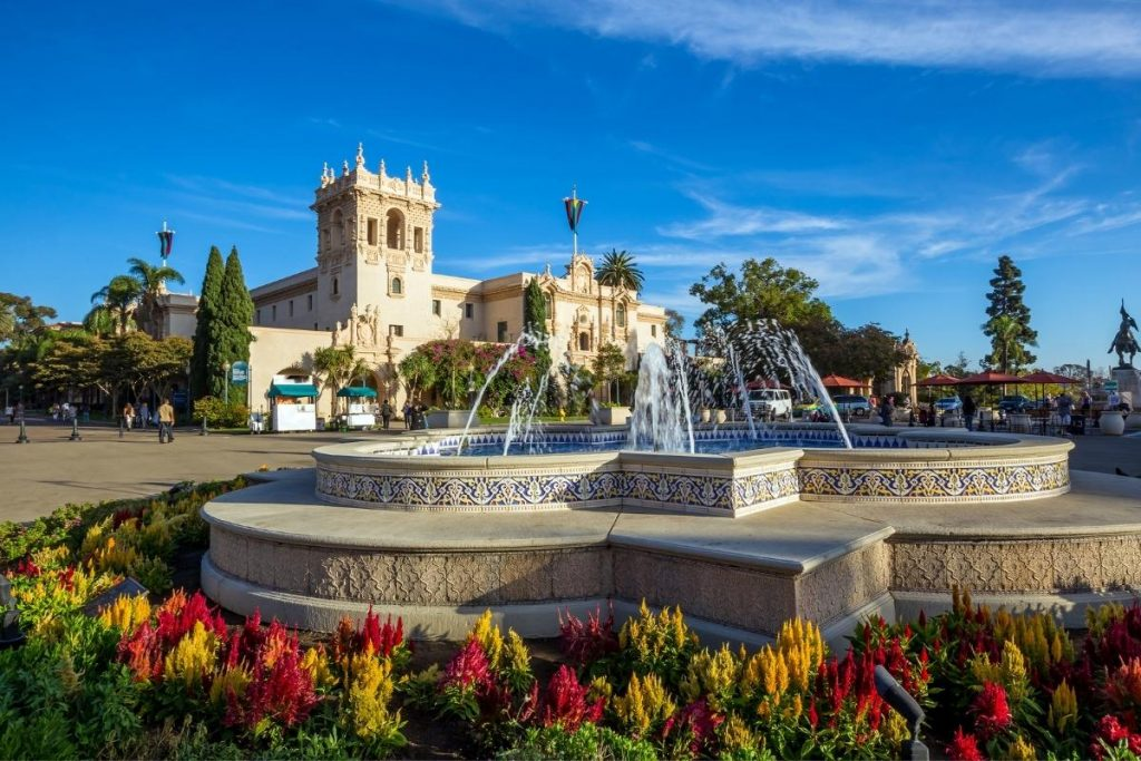 Balboa Park in San Diego - concrete fountain with beautiful blue tile on the inside and outside of fountain. 6 water spouts in the air. Classic San Diego architecture in background.